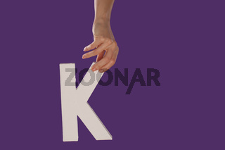 Female hand holding up the letter K from top