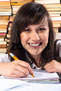 Happy student girl writing in notebook