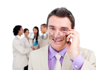 Portrait of an attractive businessman on phone in front of his team