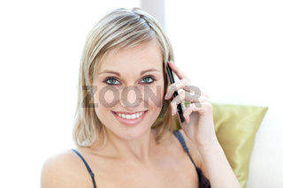 Attractive woman talking on phone sitting on a sofa