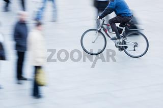Menschen beim Shoppen und ein Radfahrer