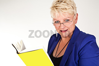 middelaged business woman in jacket with glasses reading a book