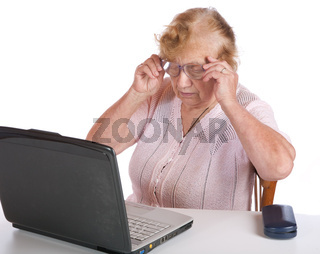 The old woman in glasses looks at the screen notebook