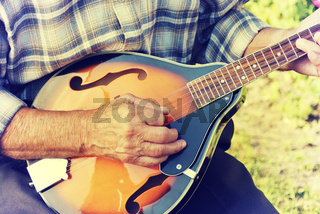 Senior man playing mandolin
