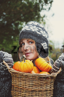 Girl holding basket of pumpkins