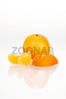 Angeschnittene Mandarine mit Spiegelung vor weißem Hintergrund
