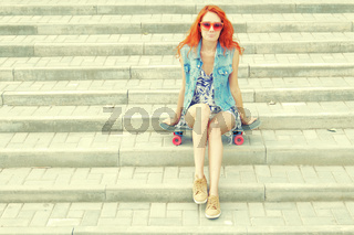 Beautiful redhead young woman sitting over a skateboard on street stairs