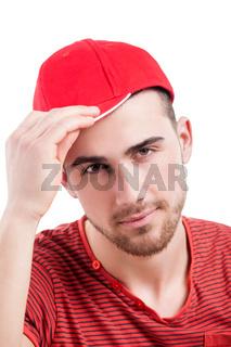 Handsome guy in baseball cap smiling at camera, wearing casual clothes, arms folded, isolated on white.?