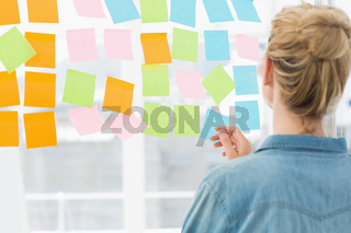 Rear view of a female artist looking at colorful sticky notes