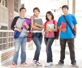 Group student holding books and standing at school