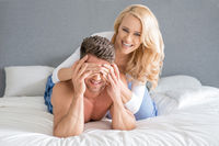Mischievous woman covering her husbands eyes