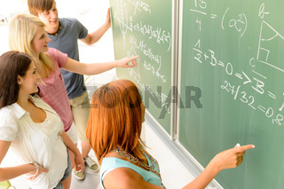 Math student write on green chalkboard classmates