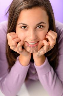 Teenage girl smiling on purple close-up portrait