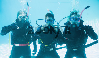 Friends on scuba training submerged in swimming pool making ok sign