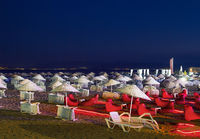 Beds and Straw Umbrellas On A Beach At Night