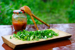 Chopped green onions on a cutting Board, on the background of two wooden spoons and banks with pepper