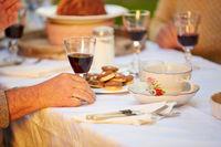 Hand mit Glas Wein am Tisch