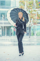 Young woman walking with an open umbrella