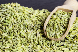 fennel seed in a wooden scoop on table