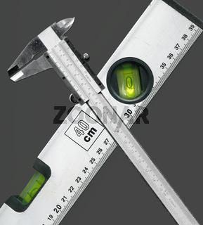 Metallische Schieblehre und Wasserwaage gekreuzt