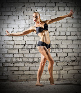 Muscular dancing woman on grey brick wall (normal version)