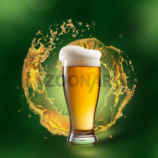Beer in glass with splash on green background