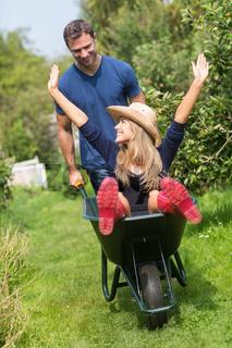 Man pushing his girlfriend in a wheelbarrow