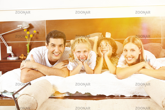 Glückliche Familie liegt im Bett mit Kindern