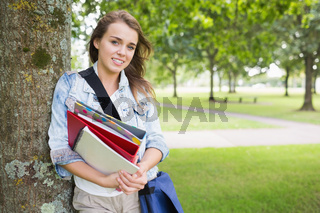 Smiling student leaning on tree holding her books