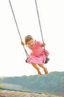 Lachendes Kind auf Schaukel im Sommer