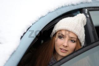 Frau schaut aus einem verschneiten Auto
