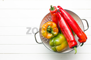 colored peppers in colander