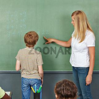 Lehrerin hilft Kind an Tafel