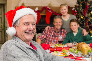 Smiling grandfather in santa hat posing in front of his family