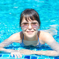Portrait of a beautiful young girl in sunglasses floating in the pool