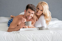 Sweet Young Caucasian Lovers on Bed Having Coffee