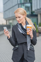 Businesswoman Busy with Phone While Having Coffee