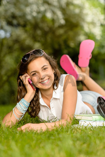 Cheerful student girl lying grass calling phone