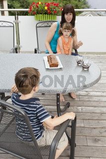 Children waiting to get a chocolate cake