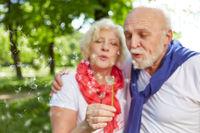 Paar Senioren pustet auf Pusteblume