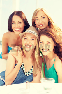 group of smiling girls in cafe on the beach