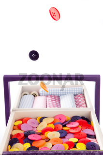 Colorful buttons fall into a sewing box