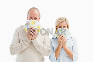 Happy mature couple smiling at camera showing money