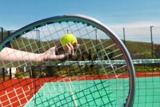 Tennis player prepares to serve a tennis ball