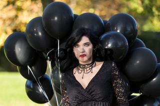 Junge Frau im schwarzen Kleid posiert mit schwarze