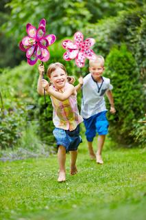 Zwei Kinder laufen im Sommer im Garten