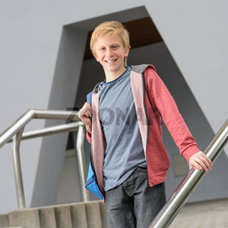 Teenage smiling student standing outside school