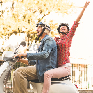 Happy mature couple riding a scooter in the city