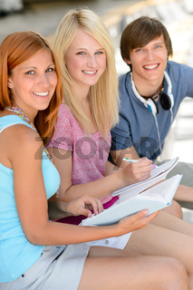 Smiling student friends sitting together studying
