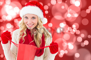 Composite image of happy festive blonde with shopping bag